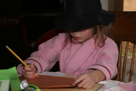 child in a witches hat writing a spell