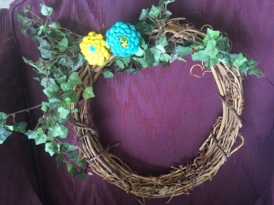 adding greenery to pine cone zinnia wreath